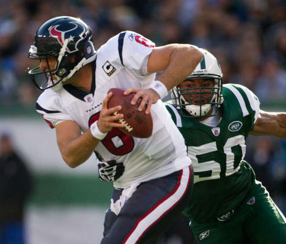 Texans quarterback Matt Schaub (8) tries to scramble away from Jets defensive end Vernon Gholston during the first quarter of Sunday's game. Photo: Smiley N. Pool, Chronicle