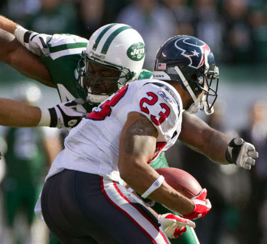 Texans running back Arian Foster (23) is brought down by Jets defensive end Shaun Ellis. Photo: Smiley N. Pool, Chronicle