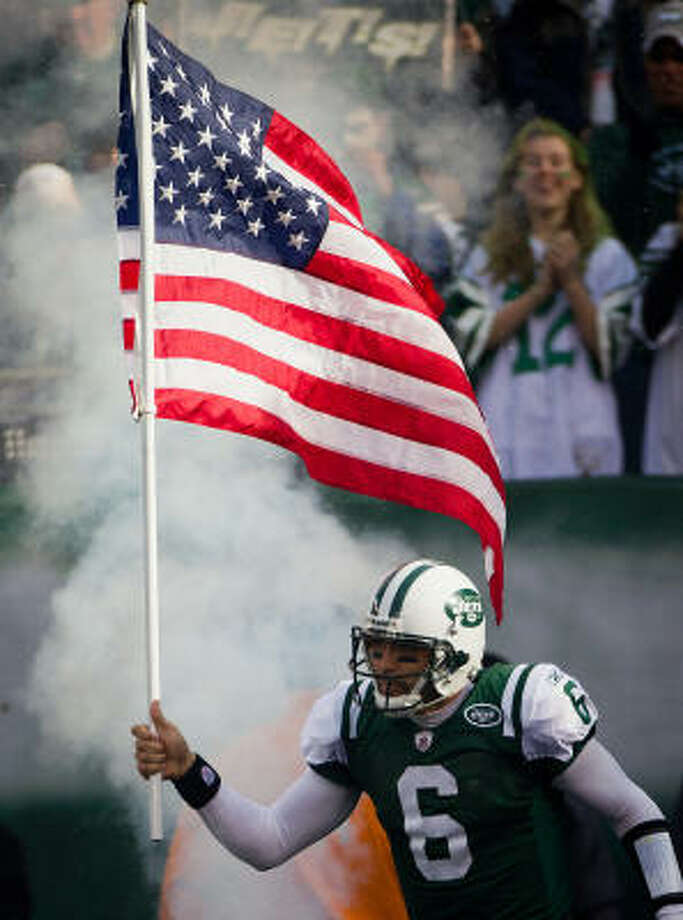 Jets quarterback Mark Sanchez carries the American flag onto the field before Sunday's game. Photo: Smiley N. Pool, Chronicle