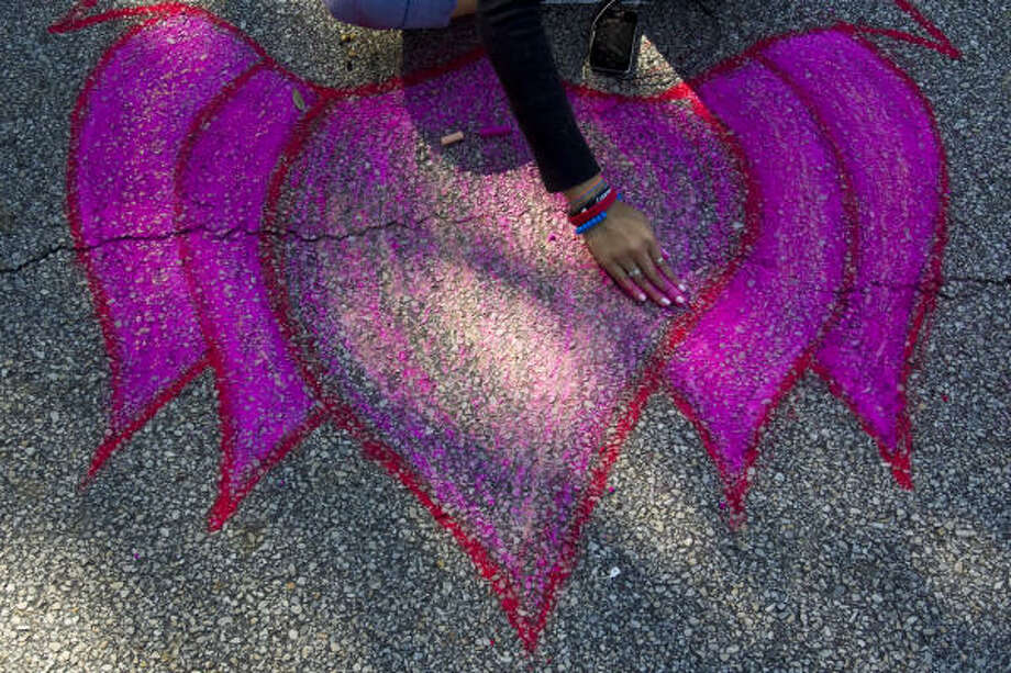 Ronda Prasit, 17, of Mount Carmel High School smooths out the chalk on a lotus flower she's drawing during the Via Colori street painting festival. Photo: Nick De La Torre, Houston Chronicle