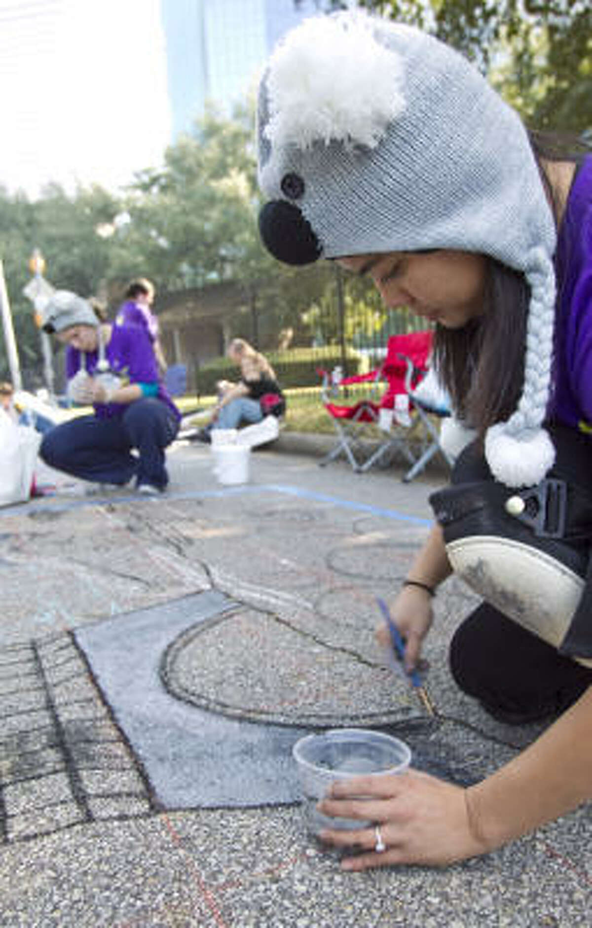 Grace Hunter, an artist and art teacher, works on her drawing Les Poison during the Via Colori street painting festival.