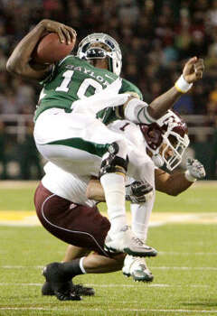 Texas A&M cornerback Trent Hunter (1) makes a hard tackle on Baylor's Robert Griffin III that forced the quarterback out of the game for one play in the third quarter. Photo: Julio Cortez, Chronicle