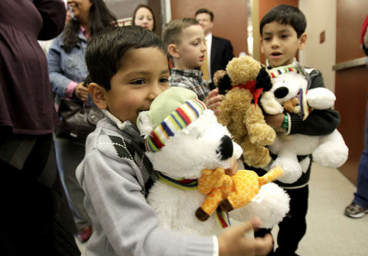 Jonathan Albus, 5, left, and his biological brother Angel Albus, 7, carry stuffed animals as they exit the 313th Juvenile Court at the Harris County Juvenile Justice Center moments after the boys were officially adopted by Jeffrey and Rebecca Albus of Katy during National Adoption Day in Houston.