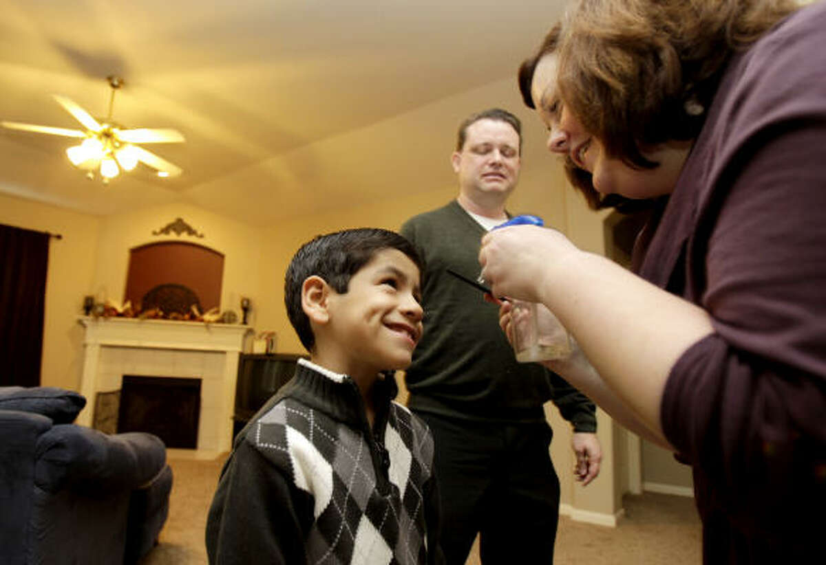 Rebecca Albus, right, combs the hair of her soon-to-be-official son, Angel, 7, as the family got ready at their Katy home to make the drive to the Harris County Juvenile Justice Center to take part of National Adoption Day.