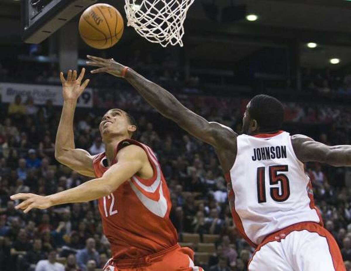 Raptors forward Amir Johnson (15) rejects Rockets guard Kevin Martin, left.