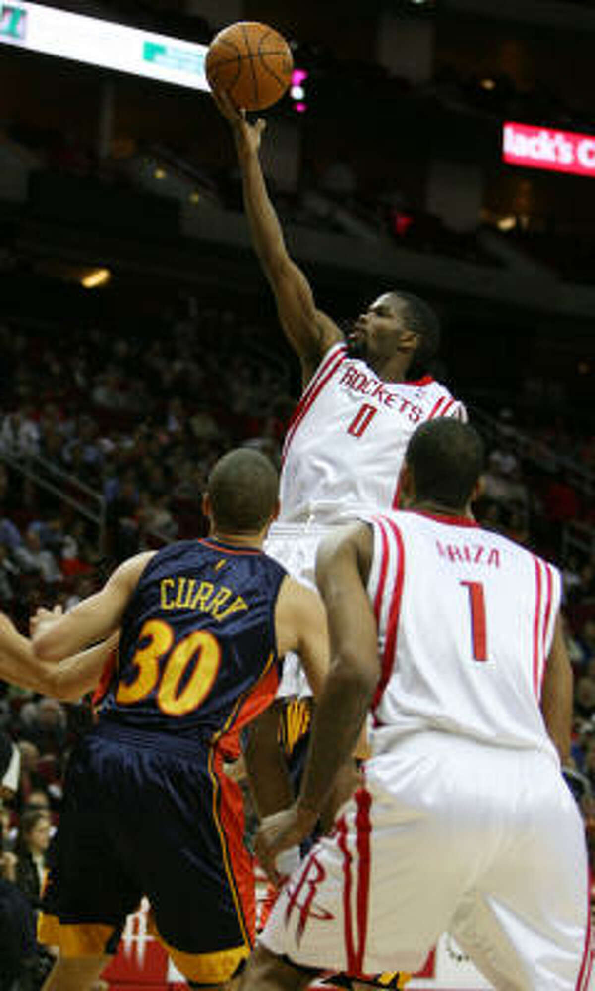 Rockets guard Aaron Brooks goes up for a finger roll over Stephen Curry.