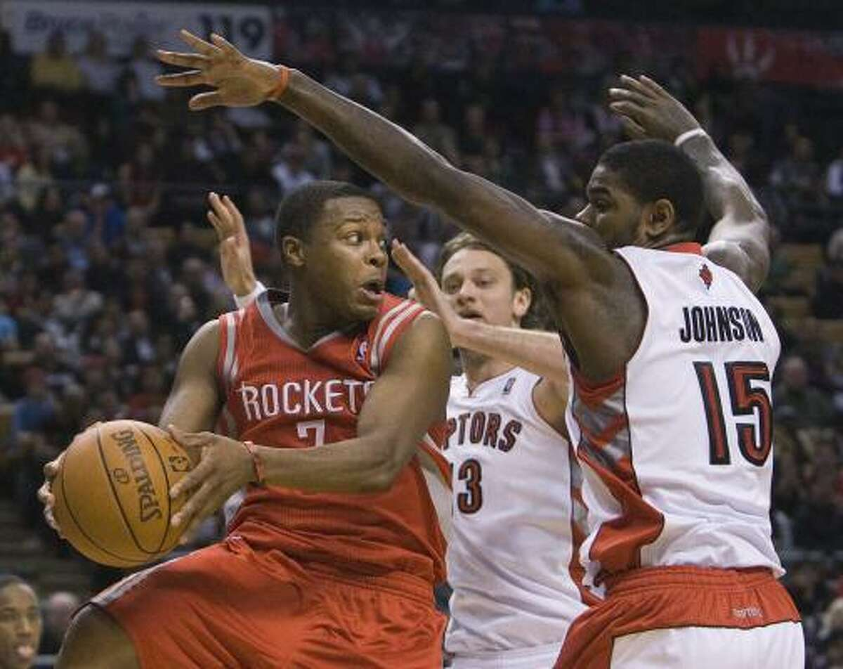 Rockets guard Kyle Lowry, left, drives past Raptors forward Amir Johnson, right.