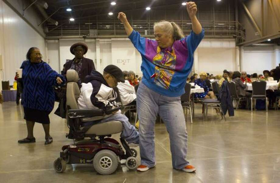 Teddy Fritscher, 64, dances with his wife, Rose Fritscher, 49, as a Zydeco song played as they joined about 3,000 seniors from various community centers, churches and senior living facilities for the 18th Annual Seniors Holiday Celebration put on by Precinct One Harris County Commissioner El Franco Lee at Reliant Center in Houston.  Seniors enjoyed a holiday meal and dancing as well as being able to donate nonperishable food items that will be donated to the nonprofit Cathedral Health and Outreach Ministries. This holiday celebration event started in 1992 with about 200 seniors who gathered at the Tom Bass Regional Park Community Center. Today, it has grown to 3,000 seniors were transported in buses from Precinct One community centers and churches. Photo: Johnny Hanson, Houston Chronicle