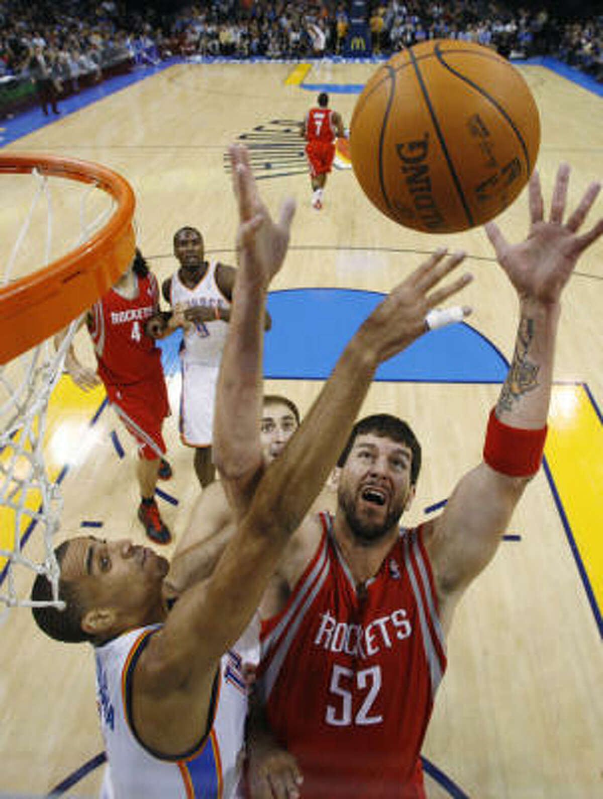 Thunder guard Thabo Sefolosha and Rockets center Brad Miller, right, battle for a rebound in the first quarter.