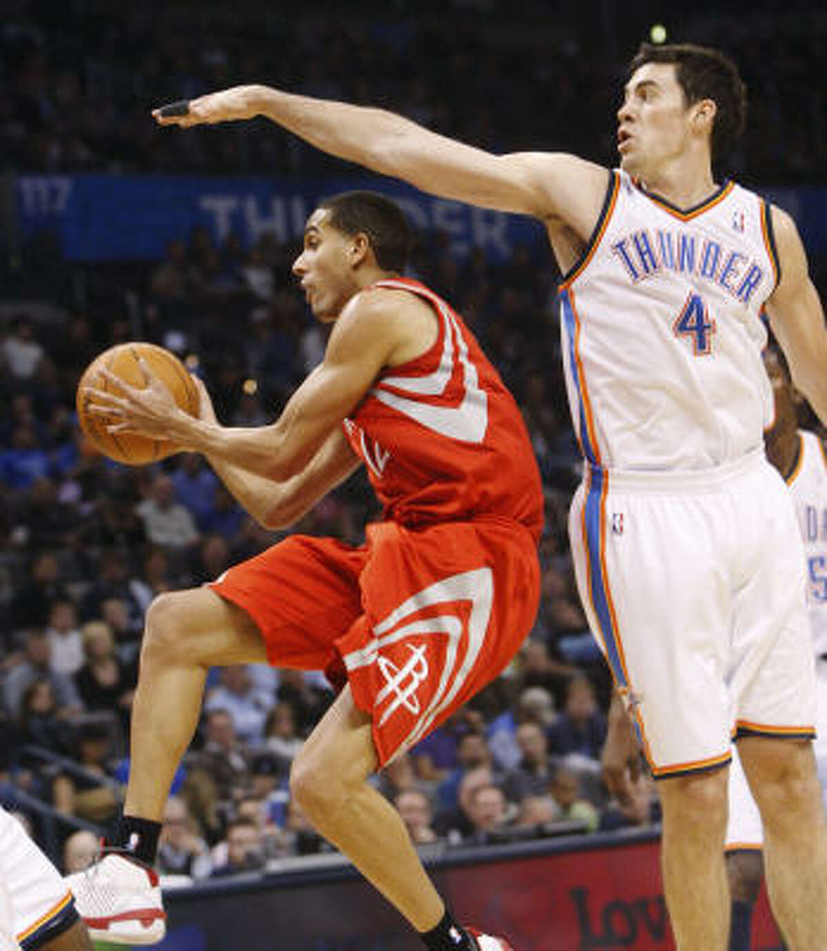 Rockets guard Kevin Martin, left, ducks under the arm of Thunder center Nick Collison in the first quarter.