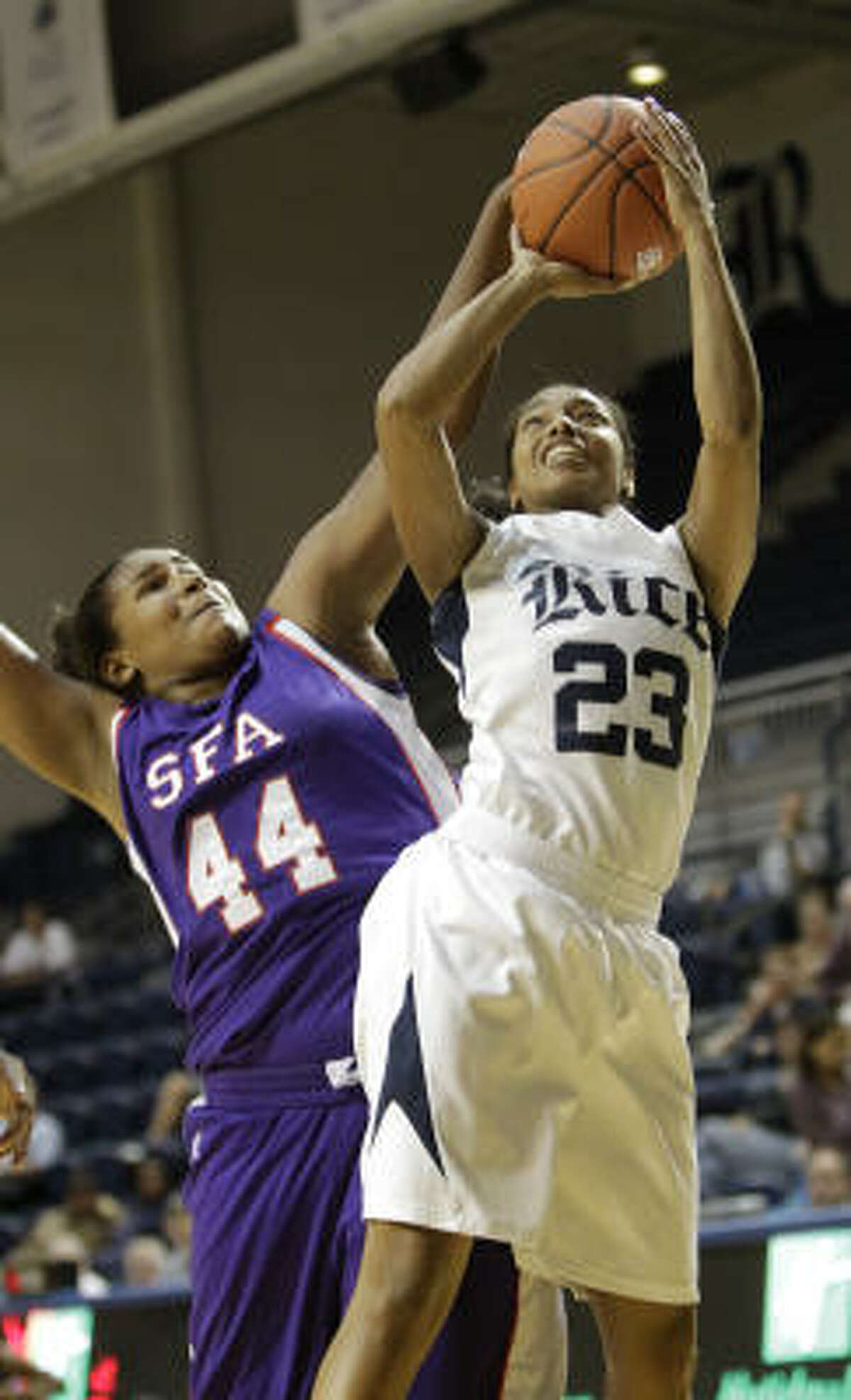 Rice's Memri Carmon (23) goes up for a basket against SFA's Chantol Drennan during the first half.