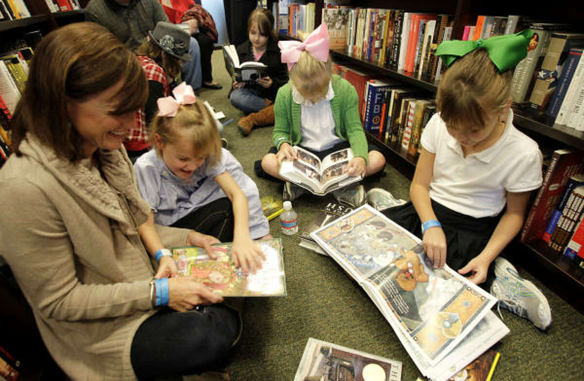Catherine Cagle, left, reads a book to her daughter Margaret, 5, as her 8-year-old twin daughters Emily, center, and Janie look over books, including Decision Points by former President George W. Bush, in Houston. Bush signed copies of his newly released memoir at the Barnes & Noble bookstore in the River Oaks shopping center.