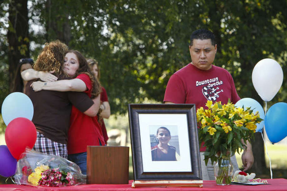"Hannah Turpin, 13, a classmate of Asher Brown, gives Amy Truong, Asher's mother, a hug as her husband David Truong, reflects as he looks towards a photo of his stepson, Asher Brown, the thirteen-year-old boy who committed suicide as a result of school bullying last week, during a memorial service near Moore Elementary School Saturday, Oct. 2, 2010, in Houston. Asher shot himself in the head with his stepfather's handgun on Sept. 23 at his family's home. Truong said his son, a straight-A student who loved to read, had been ridiculed by students at school because he was small, a Buddhist and didn't wear designer clothes. ""What my child went through was not normal in any capacity,"" Truong said. ""It was relentless. It was just day after day and nothing was done and now my son is dead."" Photo: Michael Paulsen, Chronicle"