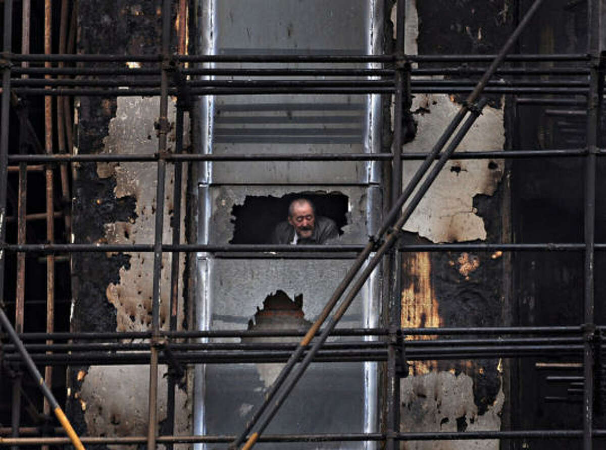 An elderly man looks out from the 28-story apartment building which was damaged by fire in the downtown area of Shanghai, east China that killed at least 53 people and left more than 70 hospitalized. The building was under renovation when it went up in flames.