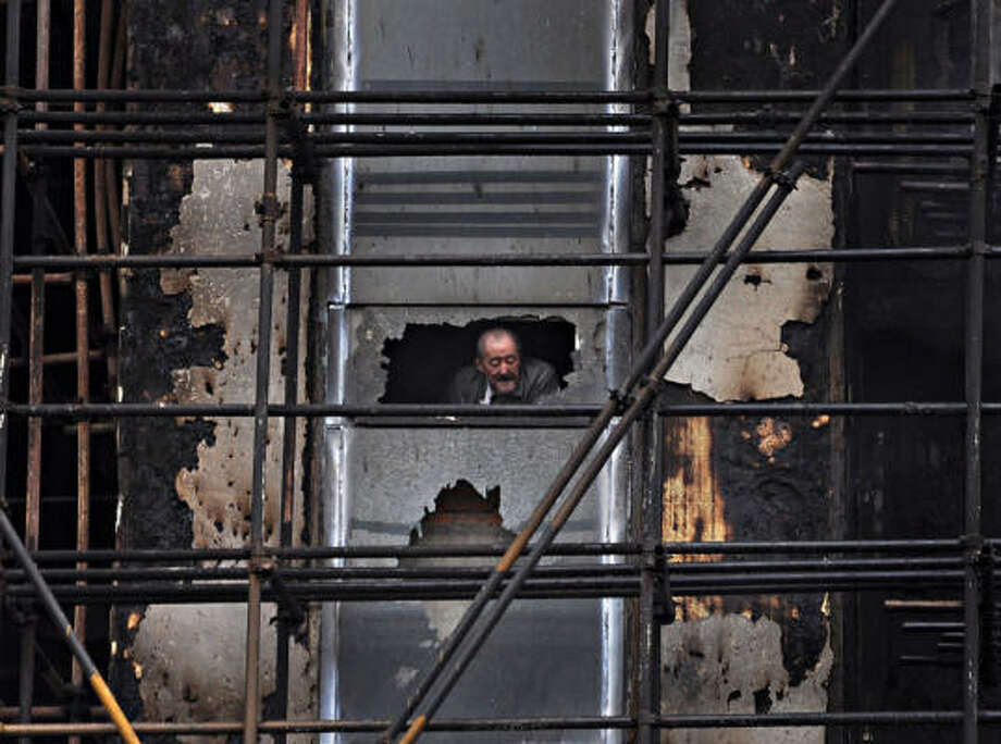 An elderly man looks out from the 28-story apartment building which was damaged by fire in the downtown area of Shanghai, east China that killed at least 53 people and left more than 70 hospitalized. The building was under renovation when it went up in flames. Photo: AP