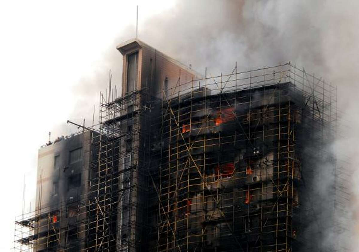 This photo taken on November 15, 2010 shows a huge fire engulfing a high-rise in Shanghai, after construction scaffolding surrounding the building initially caught fire, spreading to the building itself.