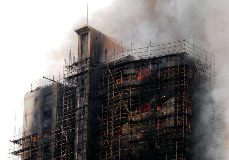 This photo taken on November 15, 2010 shows a huge fire engulfing a high-rise in Shanghai, after construction scaffolding surrounding the building initially caught fire, spreading to the building itself. Photo: AFP/Getty Images