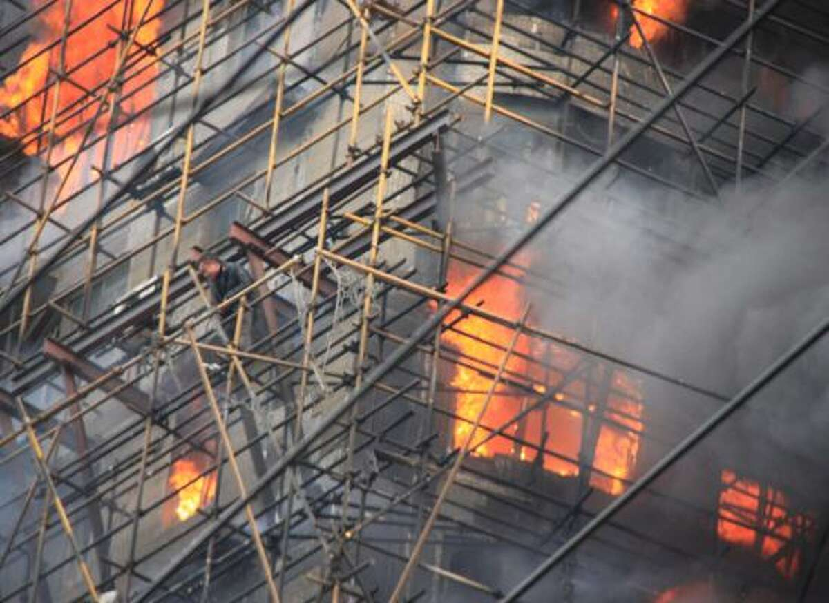 In this photo released by China's Xinhua news agency, a person waits for rescue on the apartment building on fire in the downtown area of Shanghai, east China, on Monday Nov. 15, 2010. The state news agency says the fire in the high-rise apartment building was in China's business center of Shanghai.