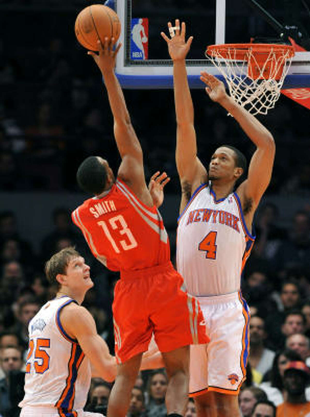 Rockets guard Ishmael Smith (13) shoots between Knicks center Timofey Mozgov (25) and forward Anthony Randolph (4) during the first quarter.