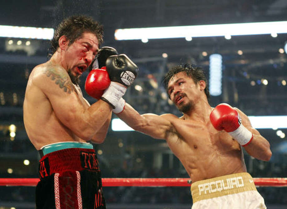 Antonio Margarito, left, reels from a blow by Manny Pacquiao in a bout for the vacant WBC super welterweight title. Photo: Richard W. Rodriguez, MCT