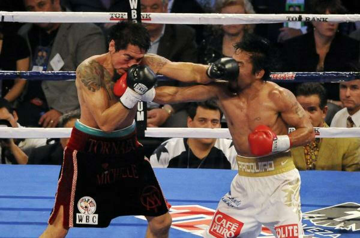 Manny Pacquiao, right, exchanges blows with Antonio Margarito.