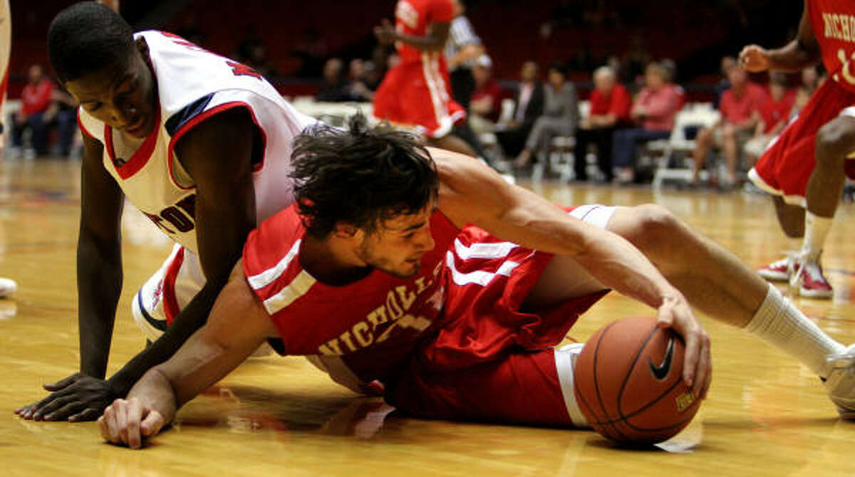 Houston's Mikhail McLean, left, and Nicholls State's Anatoly Bose, right, chase down a loose ball.