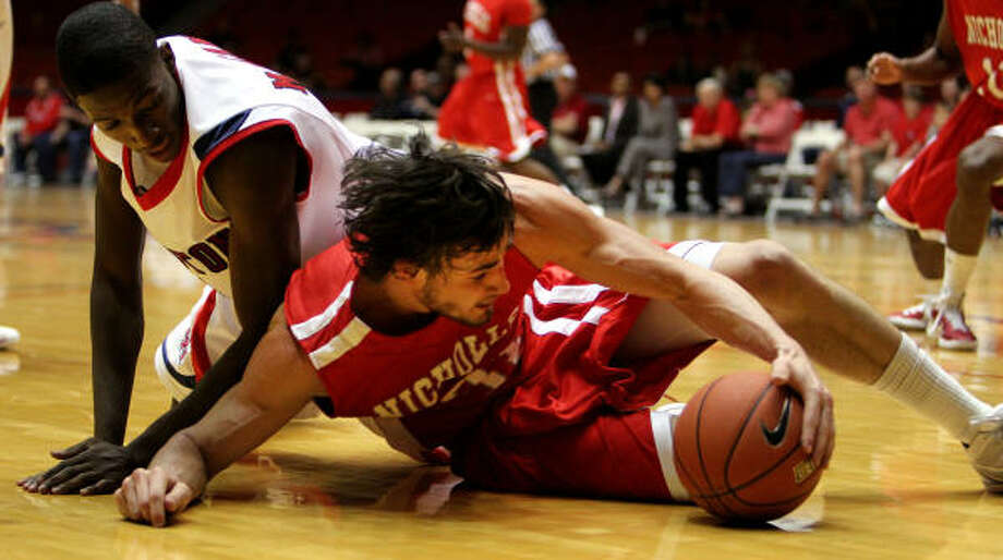 Houston's Mikhail McLean, left, and Nicholls State's Anatoly Bose, right, chase down a loose ball. Photo: James Nielsen, Chronicle