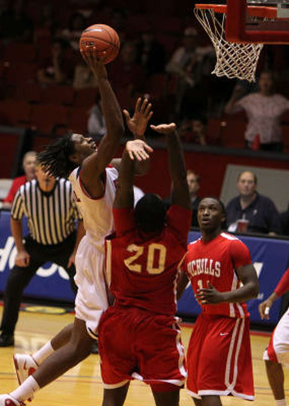 Houston's Maurice McNeil, left, scores the final basket over Nicholls State's Fred Hunter (20) in overtime.