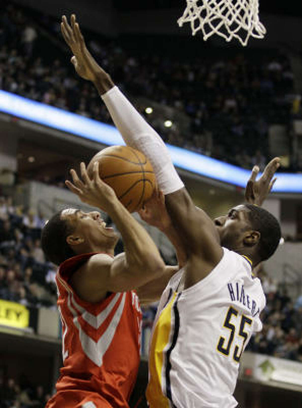 Rockets guard Kevin Martin, left, is fouled by Indiana Pacers center Roy Hibbert (55) as he goes up for a shot.