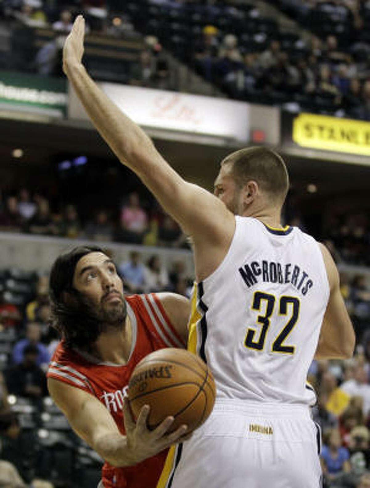Rockets forward Luis Scola, left, puts up a shot against Pacers forward Josh McRoberts.