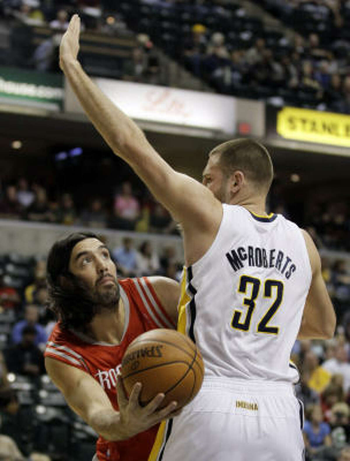 Rockets forward Luis Scola, left, puts up a shot against Pacers forward Josh McRoberts during the first quarter on Friday night.