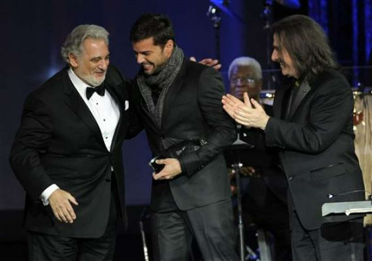 Ricky Martin, center, honors Placido Domingo, left, with the Latin Recording Academy Person of the Year award.