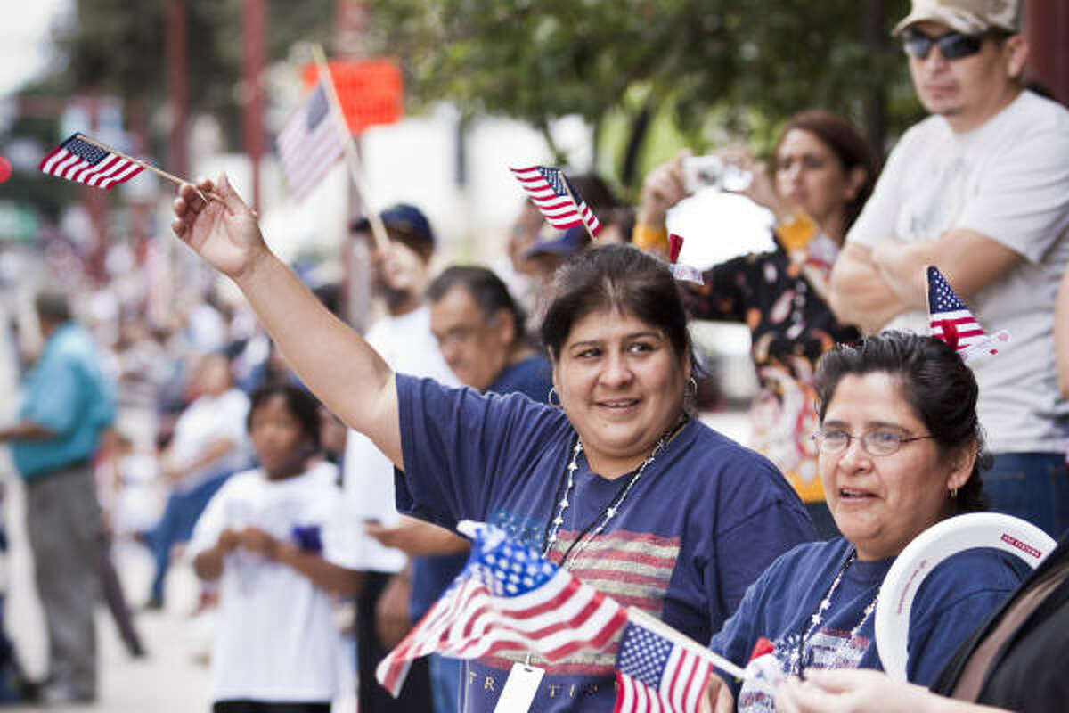 Margaret Ramos, left, and Helen Hernandez, sisters, wave to the parade in Houston. Both have family members in the Armed Services.