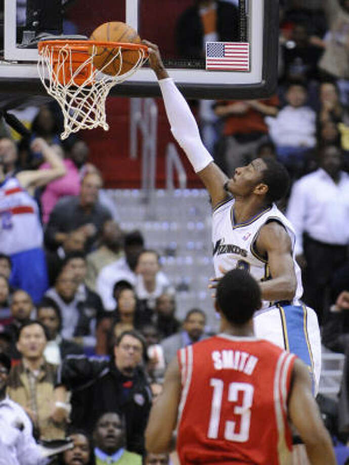 Wizards point guard John Wall, top, dunks in front of Rockets guard Ishmael Smith during the first half. Wall recorded his first professional triple-double with 19 points, 13 assists and 10 rebounds. Photo: Nick Wass, AP