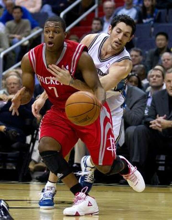 Wizards guard Kirk Hinrich, rear, tries to knock the ball away from Rockets point guard Kyle Lowry. Photo: HARRY E. WALKER, MCT
