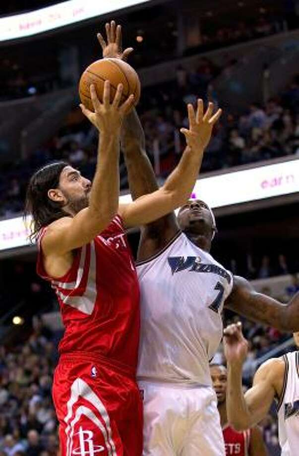 Rockets forward Luis Scola shoots over Wizards forward Andray Blatche. Photo: HARRY E. WALKER, MCT