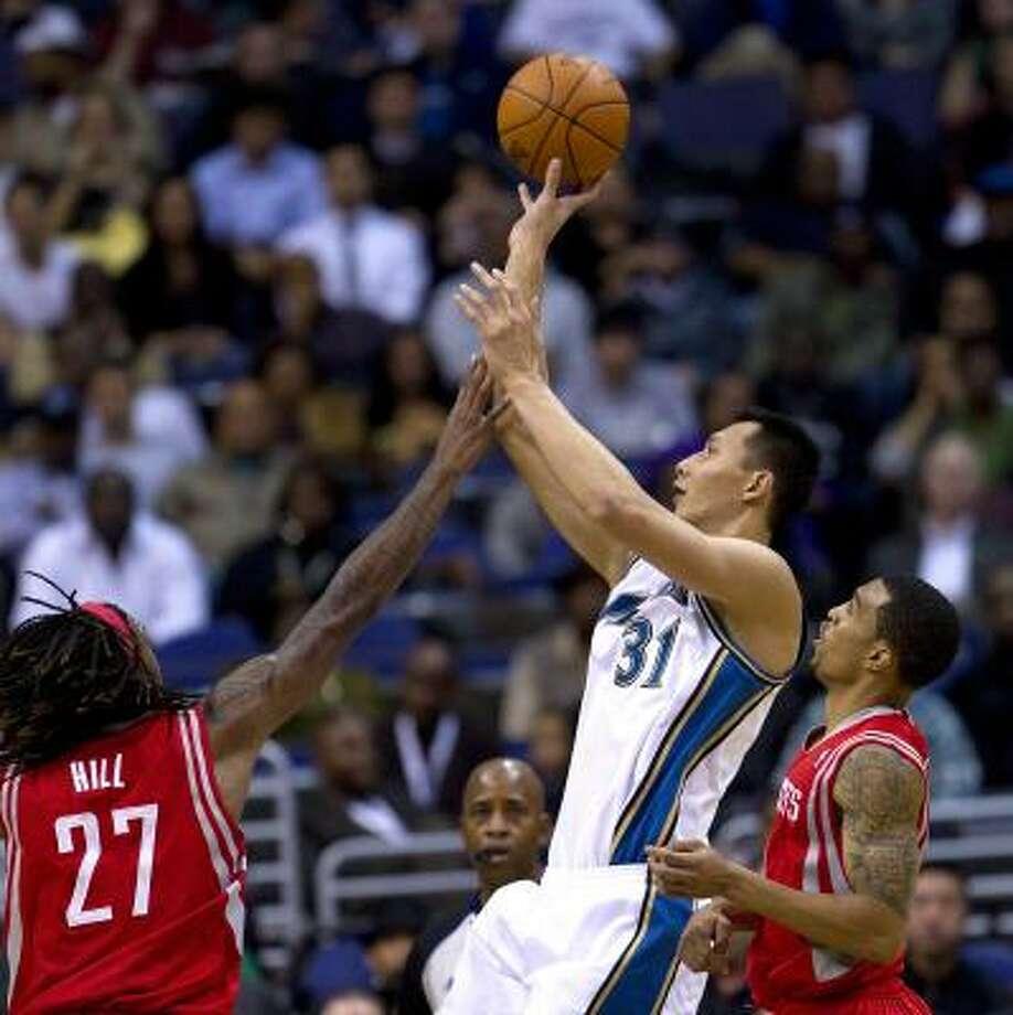 Wizards forward Yi Jianlian (31) shoots over Rockets forward Jordan Hill (27) and guard Kevin Martin. Photo: HARRY E. WALKER, MCT