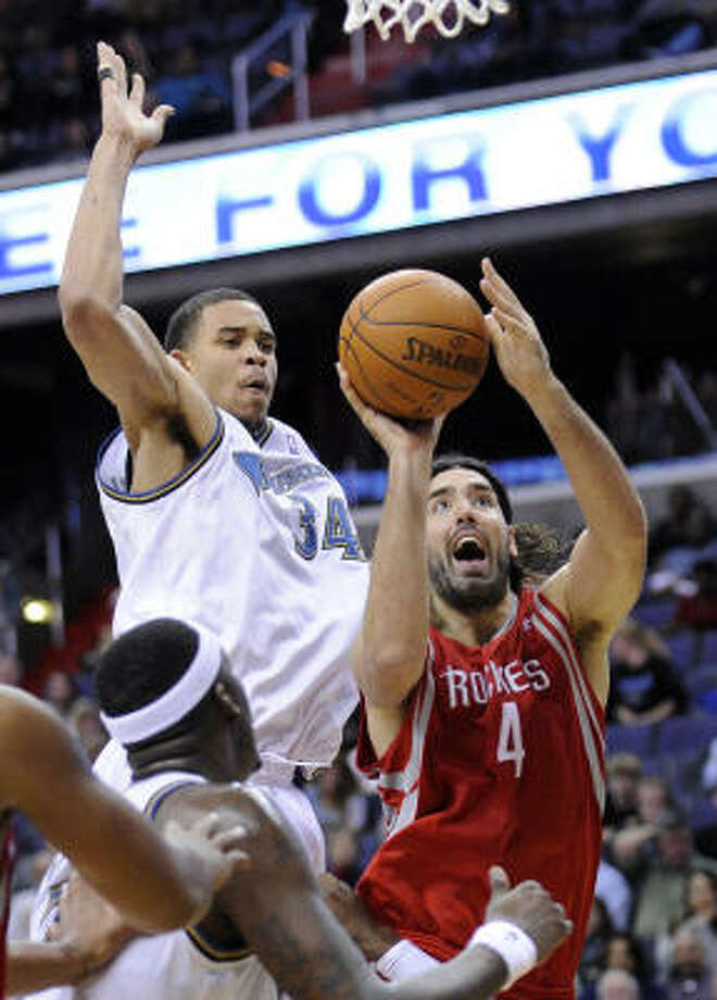 Rockets forward Luis Scola (4) goes to the basket against Wizards center JaVale McGee (34) during the first half. Photo: Nick Wass, AP