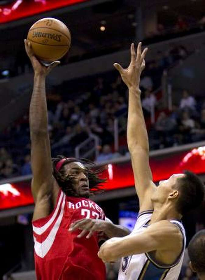 Rockets forward Jordan Hill shoots over Wizards forward Yi Jianlian. Photo: HARRY E. WALKER, MCT