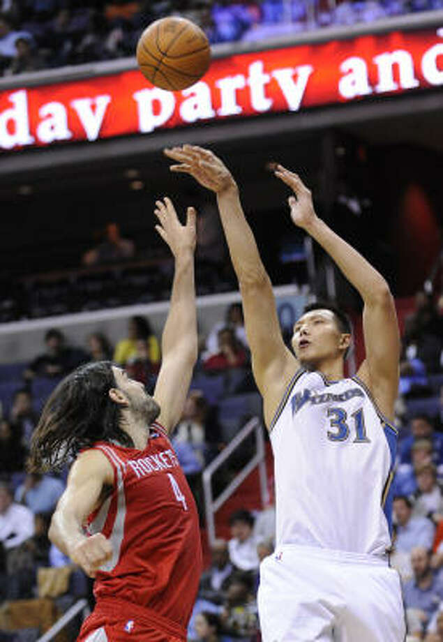Wizards forward Yi Jianlian (31) launches a shot over Rockets forward Luis Scola during the second half. Photo: Nick Wass, AP