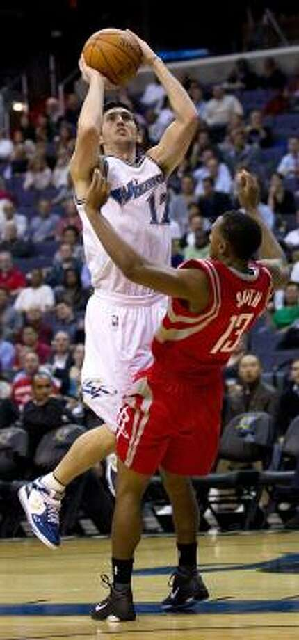Wizards guard Kirk Hinrich (12) charges into Rockets guard Ishmael Smith. Photo: HARRY E. WALKER, MCT
