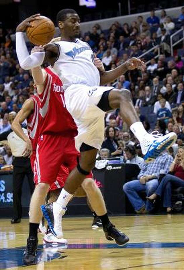 Wizards point guard John Wall is fouled on his way to the basket by Rockets forward Chase Budinger. Photo: HARRY E. WALKER, MCT