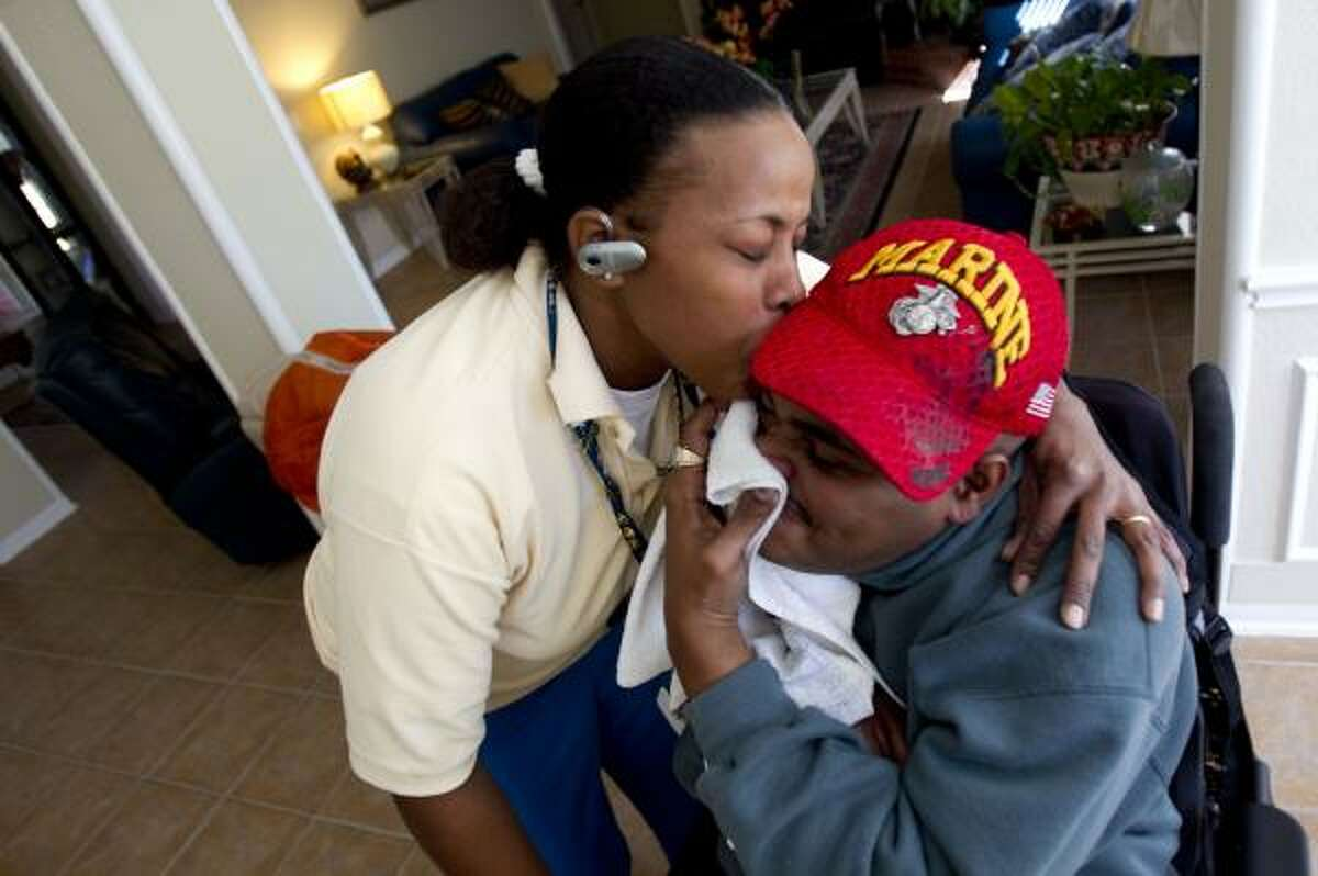 Leland Spencer tries to hide behind a towel Friday as his sister Lianne Spencer plants a playful kiss on his face at their mother's home in northeast Houston. The twins are 39 and share more than a birthday. Like him, she's also a veteran.
