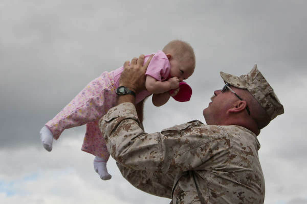 Marine Gunnery Sergeant Ronald Laxton kisses the top of his 8-month-old daughter's head while waiting for a bus at the Armed Forces Reserve Center at Ellington Field before engaging in pre-deployment training at Camp Pendleton in California. Marines assigned to the 1st Battalion, 23rd Marine Regiment, 4th Marine Division, also known as the