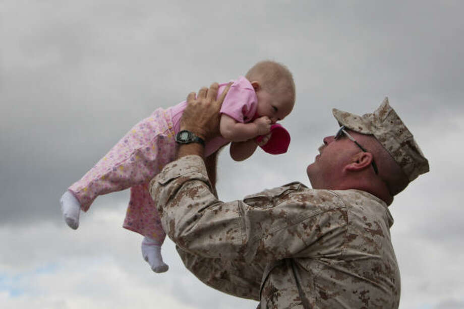 "Marine Gunnery Sergeant Ronald Laxton kisses the top of his 8-month-old daughter's head while waiting for a bus at the Armed Forces Reserve Center at Ellington Field before engaging in pre-deployment training at Camp Pendleton in California. Marines assigned to the 1st Battalion, 23rd Marine Regiment, 4th Marine Division, also known as the ""The Lone Star Battalion"", leave for pre-deployment training at Camp Pendleton in California.  The group will then deploy early next year in support of the II Marine Expeditionary Force in southwestern Afghanistan. Photo: Michael Paulsen, Houston Chronicle"