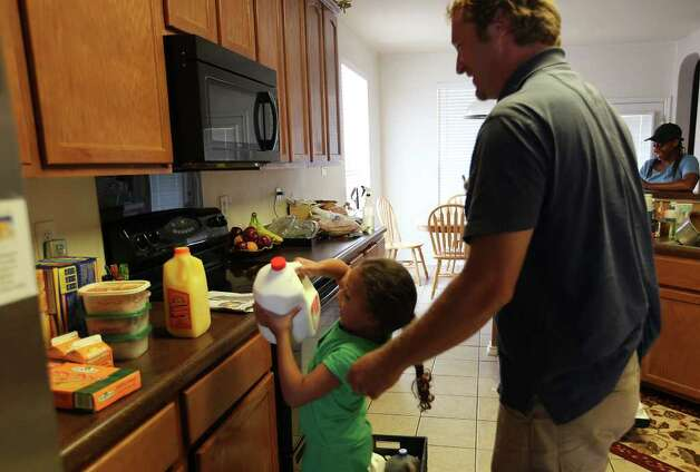 Five-year-old Ki Robertson helps Darren Chelin while he makes his daily deliveries of dairy products. Photo: JERRY LARA, San Antonio Express-News / SAN ANTONIO EXPRESS-NEWS