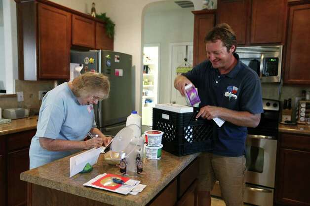Darren Chelin talks with customer Alice Serafin while making deliveries. Photo: JERRY LARA, San Antonio Express-News / SAN ANTONIO EXPRESS-NEWS