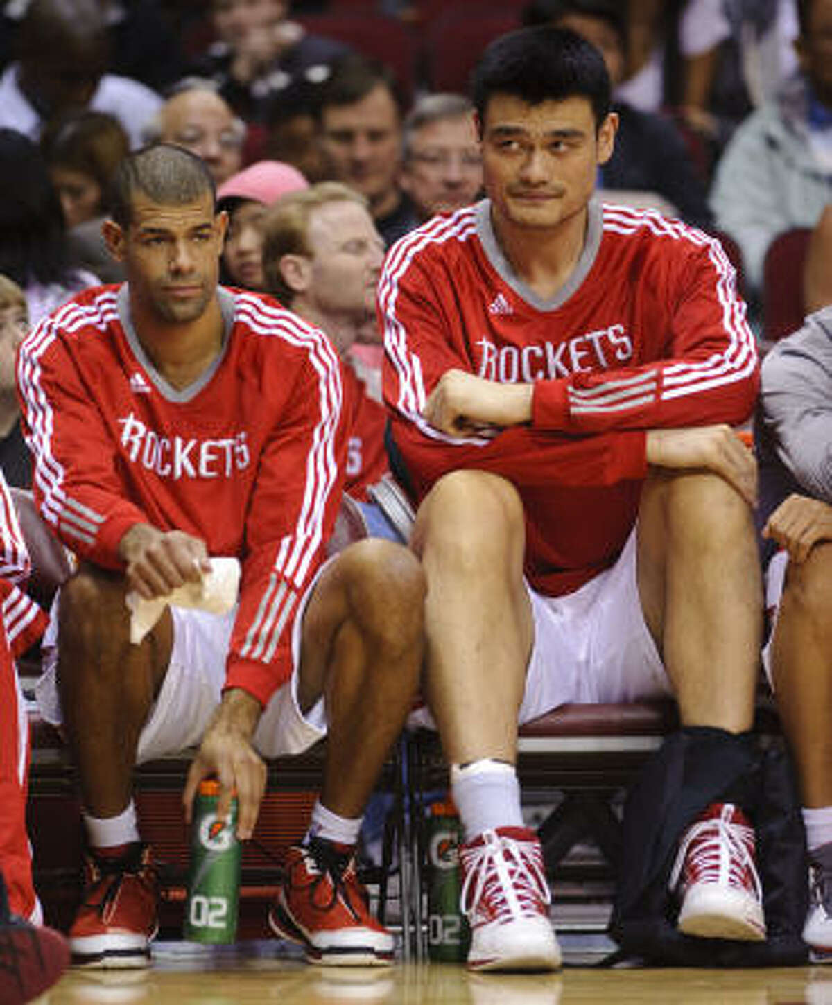 Rockets center Yao Ming, right, sits with his left foot wrapped on the bench during the second quarter.