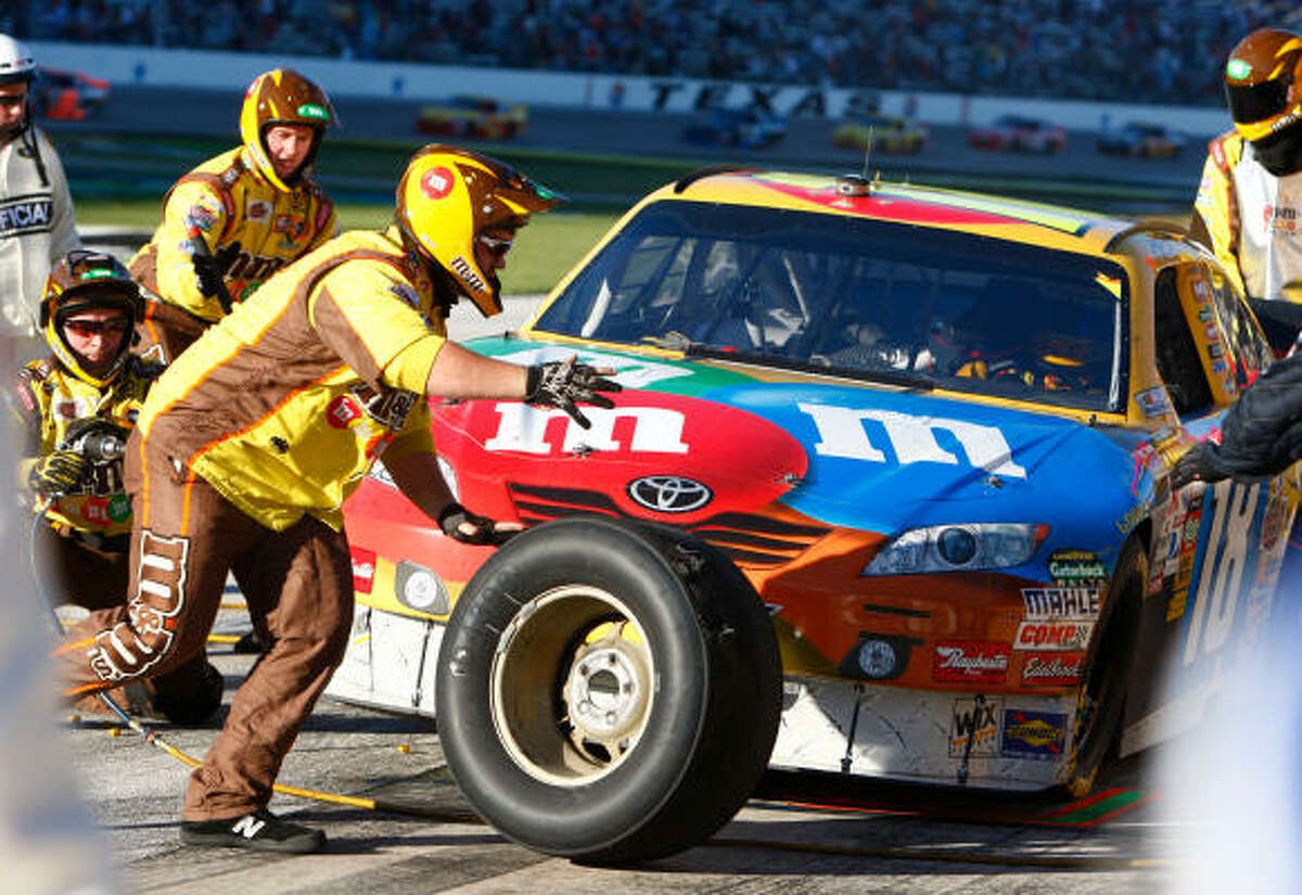Kyle Busch's car gets worked on in the pits after spinning out in turn two of the NASCAR AAA Texas 500. Busch was penalized for speeding when leaving the pits after the stop, then penalized again after making an obscene gesture toward TV cameras during the first penalty.