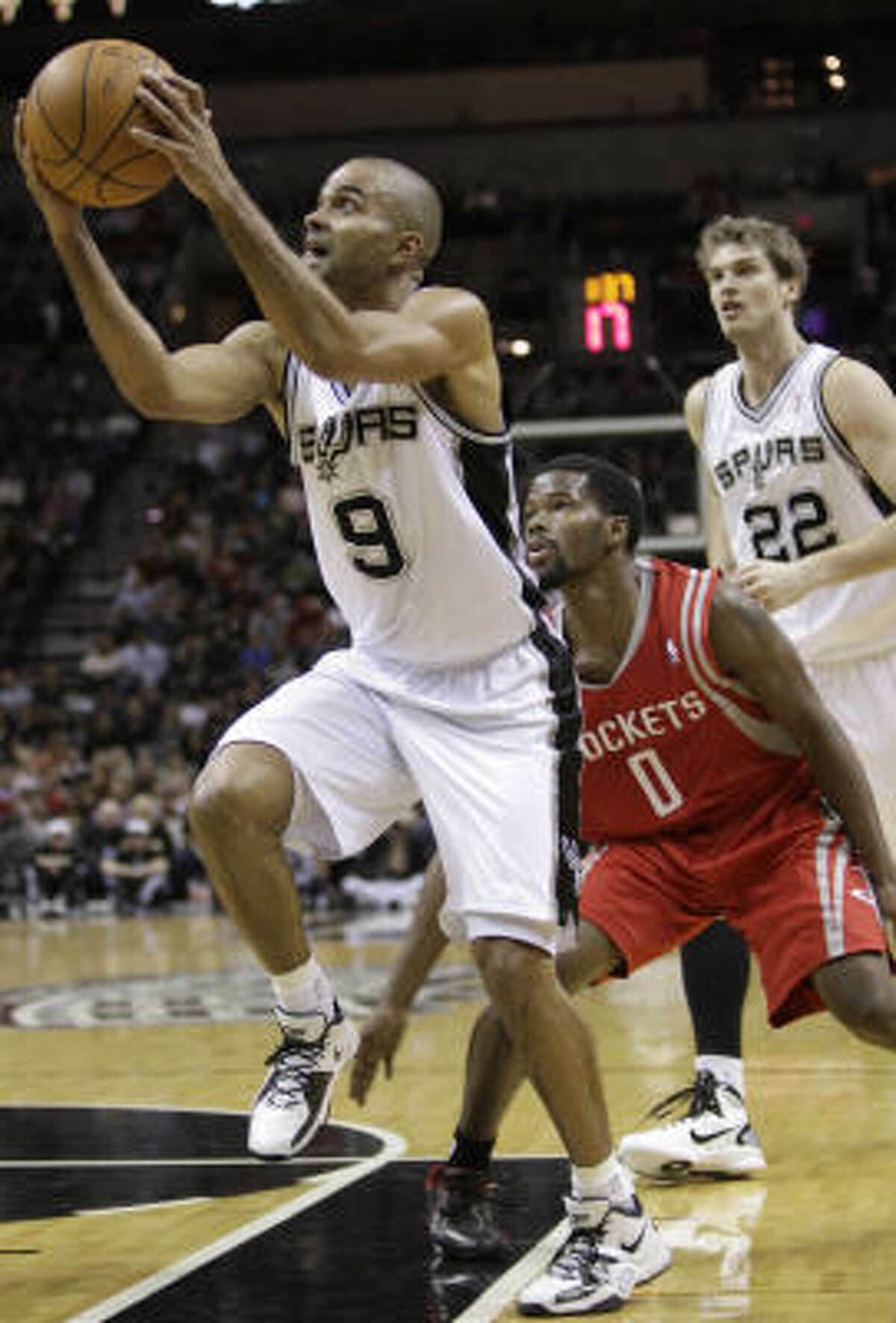 Spurs guard Tony Parker looks to put up the shot in front of Rockets guard Aaron Brooks during the first quarter.